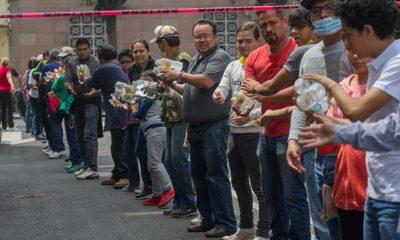 Ciudadanos continúan realizando donaciones de agua y alimentos, en la calle de Bretaña, en la colonia Zacahuitzco. FOTO: ISAAC ESQUIVEL /CUARTOSCURO.COM
